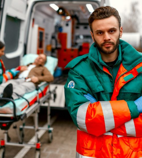 male-paramedic-in-uniform-stands-with-his-arms-crossed-in-front-of-an-ambulance-and-his-colleague-standing-near-patient-s-gurney