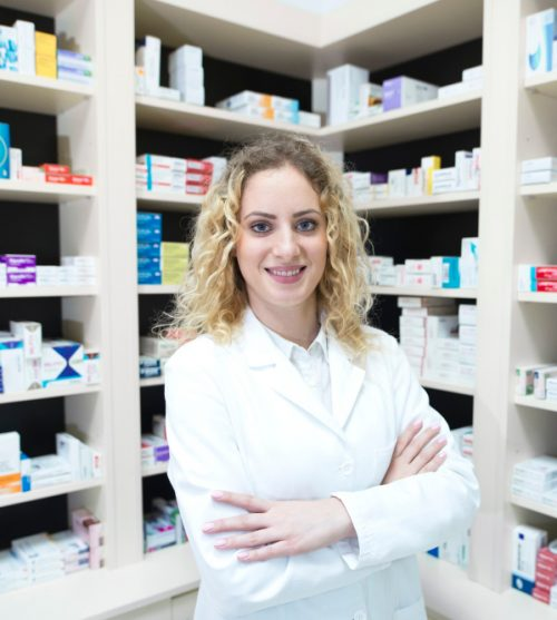 portrait-of-female-pharmacist-in-drug-store-standing-in-front-of-shelves-with-medications