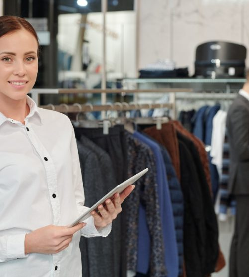 portrait-of-smiling-attractive-sales-consultant-in-white-blouse-using-digital-tablet-in-clothing-shop