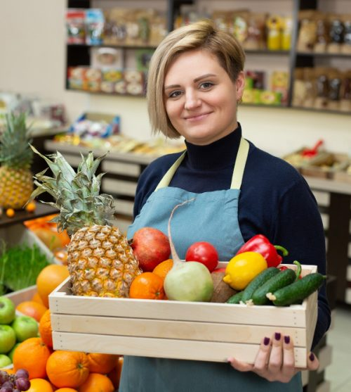 smiling-woman-salesman-holds-wooden-box-with-vegetables-and-fruits-in-the-store