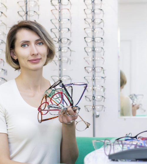 young woman in optic store choosing new glasses with optician. glasses in the store of optics. A woman chooses glasses. many glasses in hand. Ophthalmology.